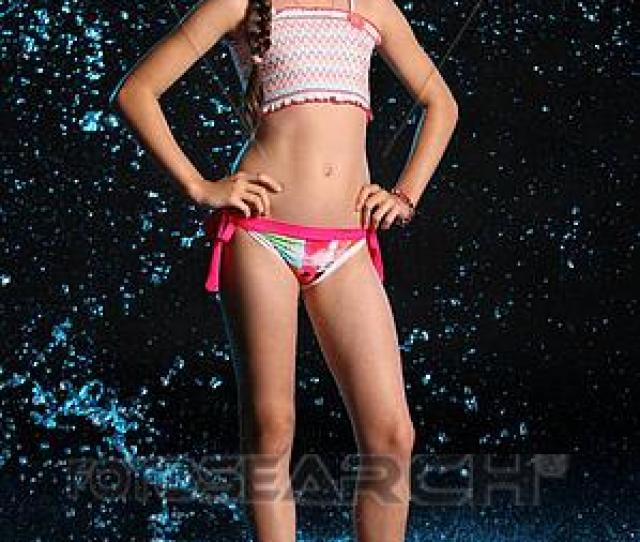Adorable Young Teenage Girl In A Swimsuit Stands Barefoot In Splashing Water Pretty Child With Dark Hair Beautiful Face And A Slim Figure Slender Preteen