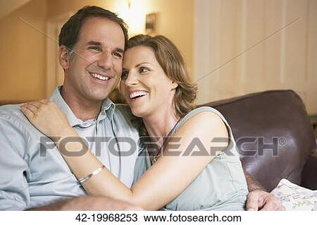 Stock Photo - Husband and wife sitting on a couch. Fotosearch - Search Stock Images, Poster Photographs, Pictures, and Clip Art Photos