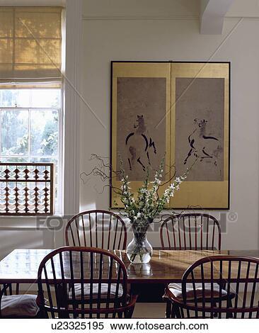 dorure encadre chinois dessin sur mur de blanc salle manger a simple bois table et windsor preside banques de photographies