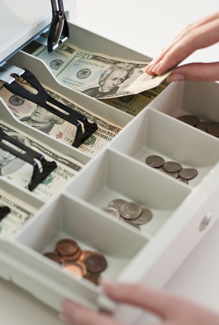 Woman removing money from cash register, close-up