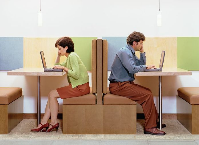 Man and woman back to back in separate booths using laptop computers