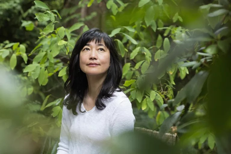 Japanese woman sitting in garden