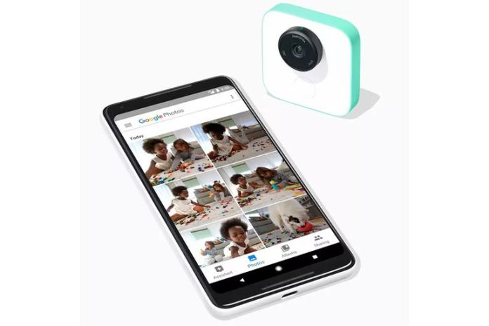 The Google Clips camera next to a smartphone showing photos taken by the camera