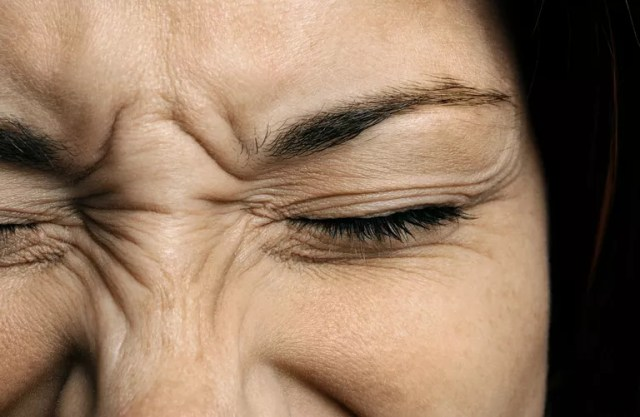 Close up of a woman's face, wrinkled up in pain.