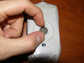 Picture of someone removing the trackball from a computer mouse