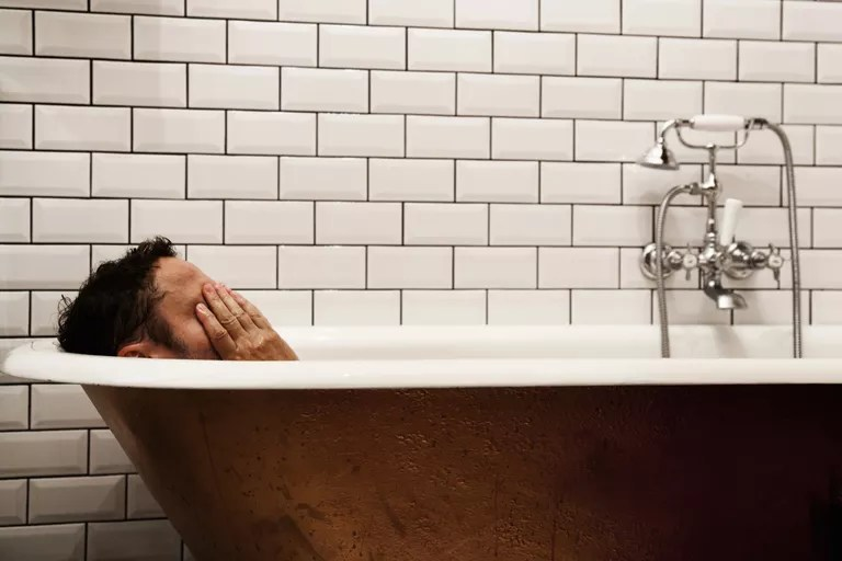 Stressed man tries to relax in the bath