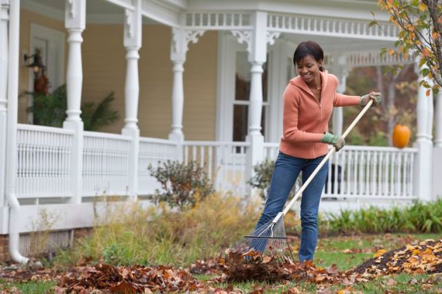 woman raking leaves in front of house