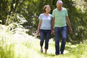 Older couple walking in the woods to stay healthy in order to ease arthritis