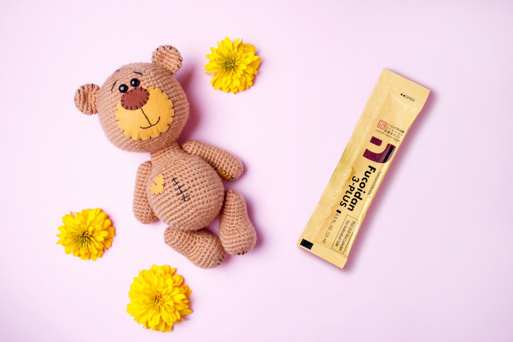 Amigurumi handmade teddy bear with yellow chrysanthemum isolated on a pink background. Baby background. Copy space, top view.