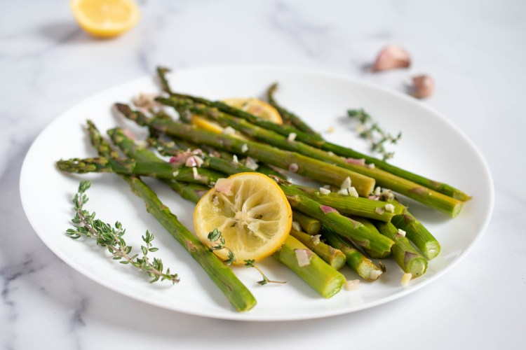 A plate of asparagus with lemon and thyme