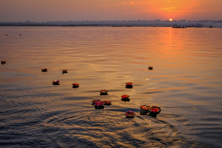 Sunrise on the Ganges at Varanasi, Uttar Pradesh, India. Garlands of flowers and candles given as offerings float on the river as the sun rises.