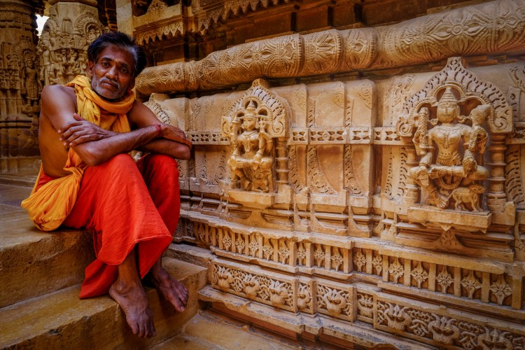 A monk sits on the steps at a Jain Temple in Jaisalmer, India. The temple, which was constructed in the 12 century, is built of yellow sandstone and is famous for its intricate stonework.