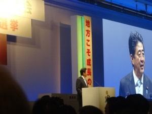 党大会での安倍総理の演説。大きな画面にも映され、広い会場の後ろからも様子が見えます。