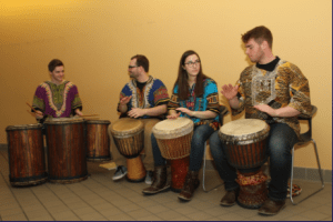Four students playing the drums