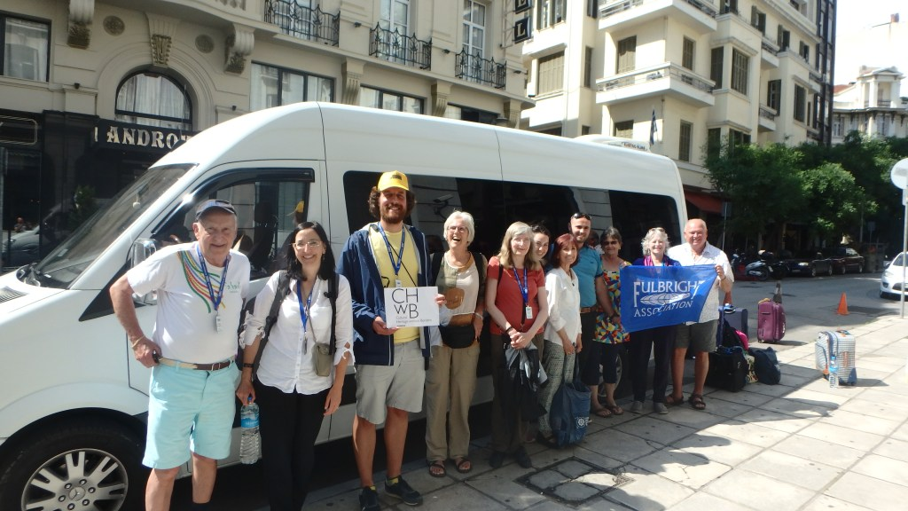 A group of smiling travelers stand outside a van. They are holding a Fulbright Association banner and a placard for Cultural Heritage Without Borders.