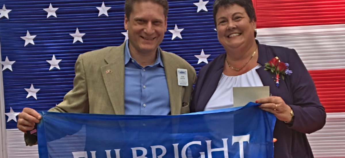 Kim Eger and Ambassador Palmer in front of American flag holding Fulbright banner
