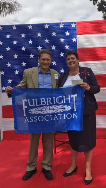 Kim and Ambassador Palmer standing in front of American flag holding the Fulbright banner