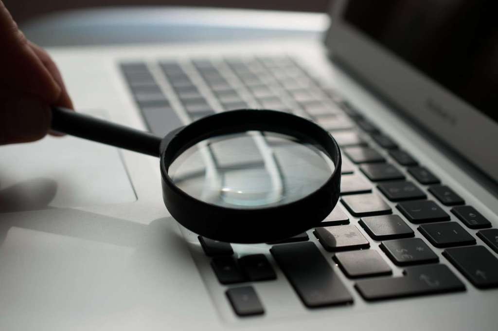 magnifying glass near gray laptop