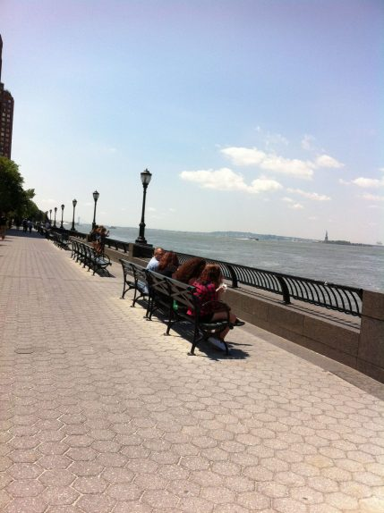Battery Park Walkway along the Hudson River with the Statue of Libery in the Background