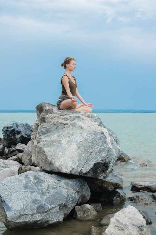 concentrated yoga teacher meditating on large stone