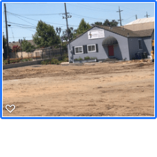 Brown dirt vacant lot, blue building behind it, green trees and telephone poles line the street.,