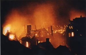 Fire at night, numerous two story houses burning, flames into night sky