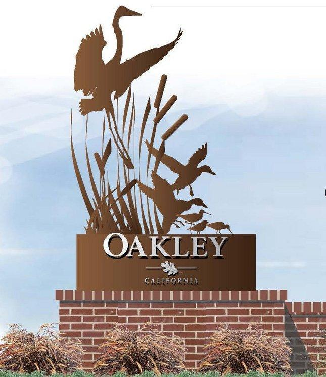 sculpture of birds landing on a river, brown in color, brown base with the words Oakley California, brick structure below that