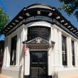 corner building, ornate, black overhang, white marble (maybe stucco) American flag in front