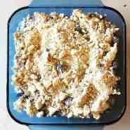 blueberry crisp dessert in a blue glass baking dish