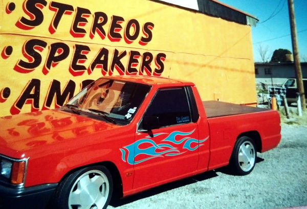 Orange mini-truck with teal flame graphics