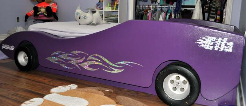Purple race-car bed with glitter graphics on the sides.
