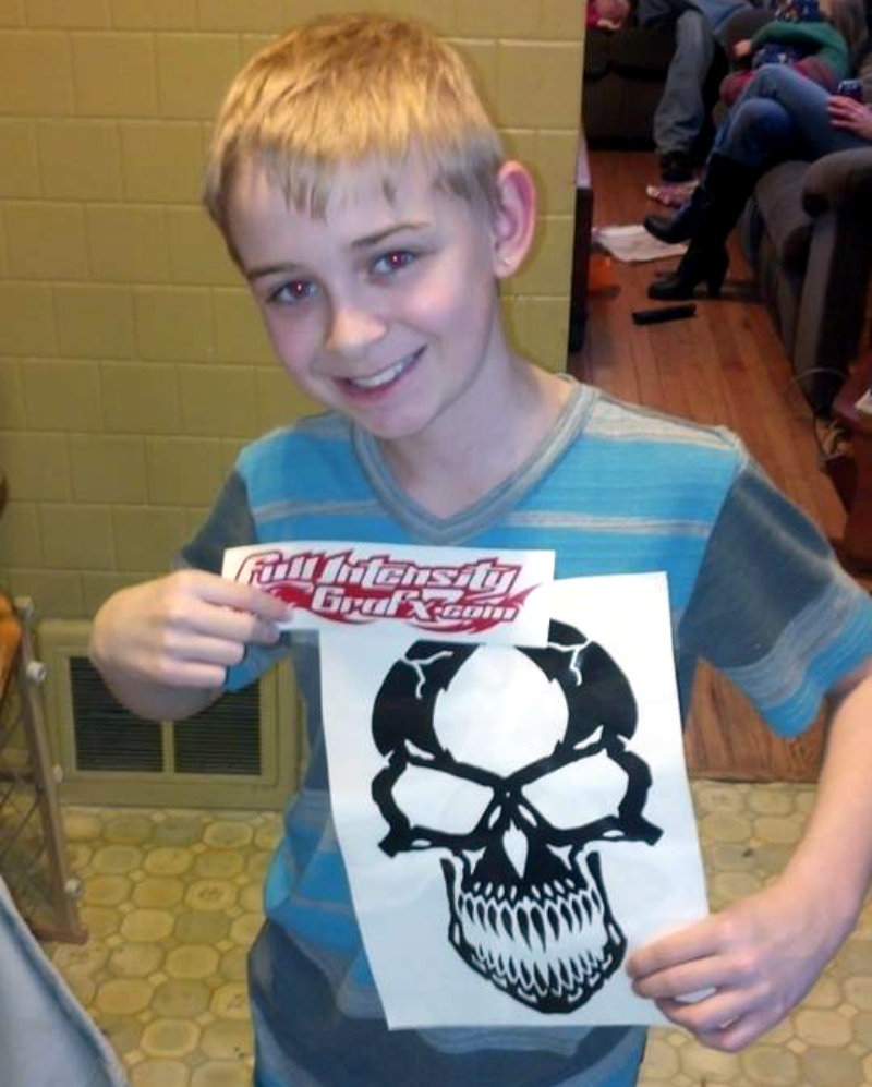 Kid posing with black skull decal and red Full Intensity Grafx decal