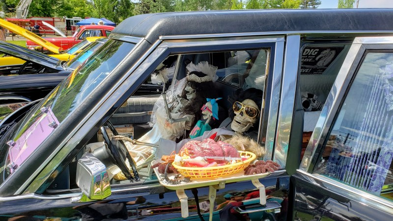 Skeletons inside of a Hearse, with food, brains, on the side window