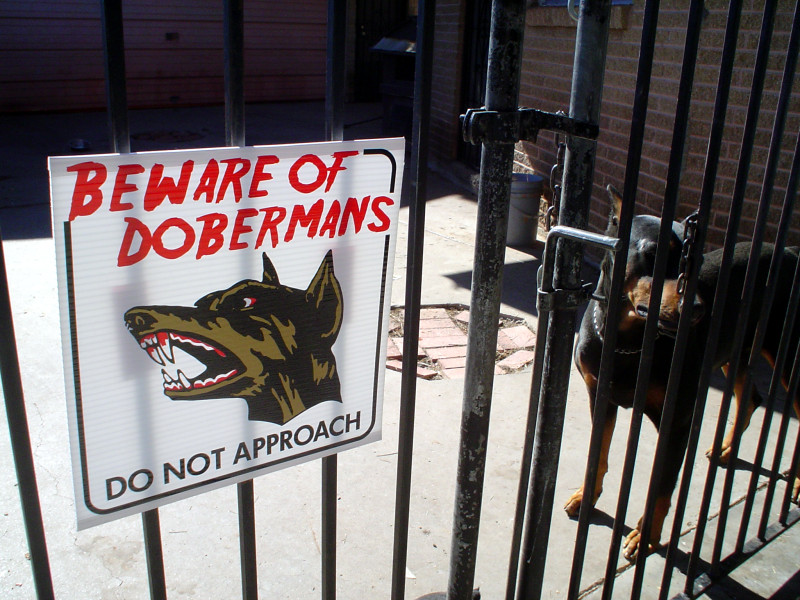 Beware of dog sign and doberman