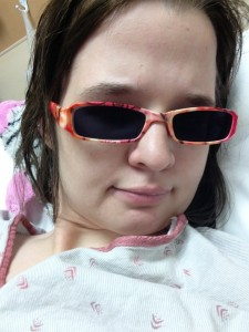 Image is of me nearly a year ago, wearing sunglasses and in a hospital gown.