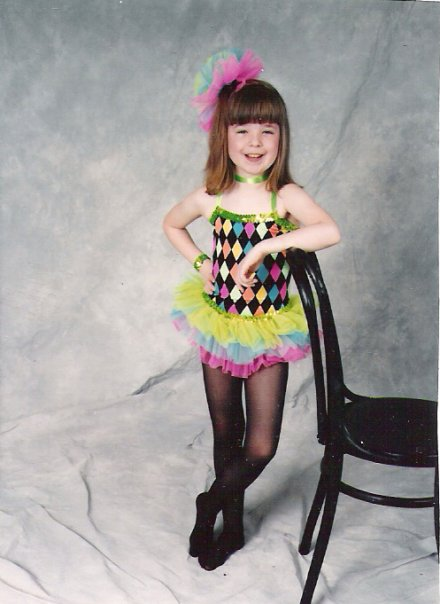 Image is of a smiling eight year old female child. She has full bangs/fringe and shoulder length brunette hair. She is wearing a multicolor leotard with a tutu, black tights, and a multicolor bow. She is grinning and leaning against a chair.