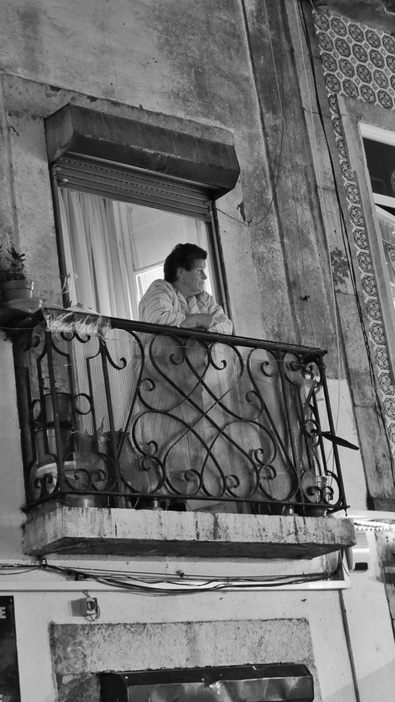 A woman surveils the Bairro Alto on a warm December night from her balcony. I love spying on people who are spying on people.