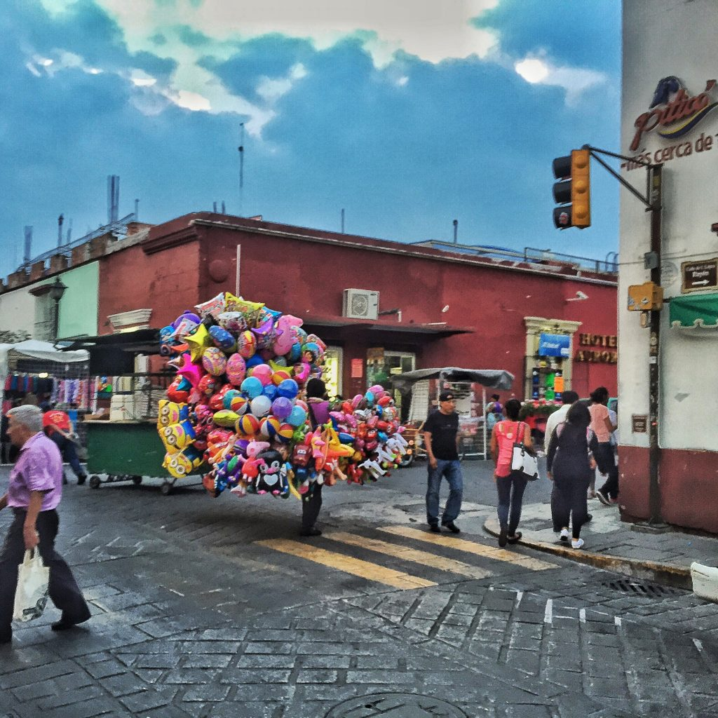 Balloon guy battles brisk winds and narrow streets en route to the zocalo to sell balloons to families.