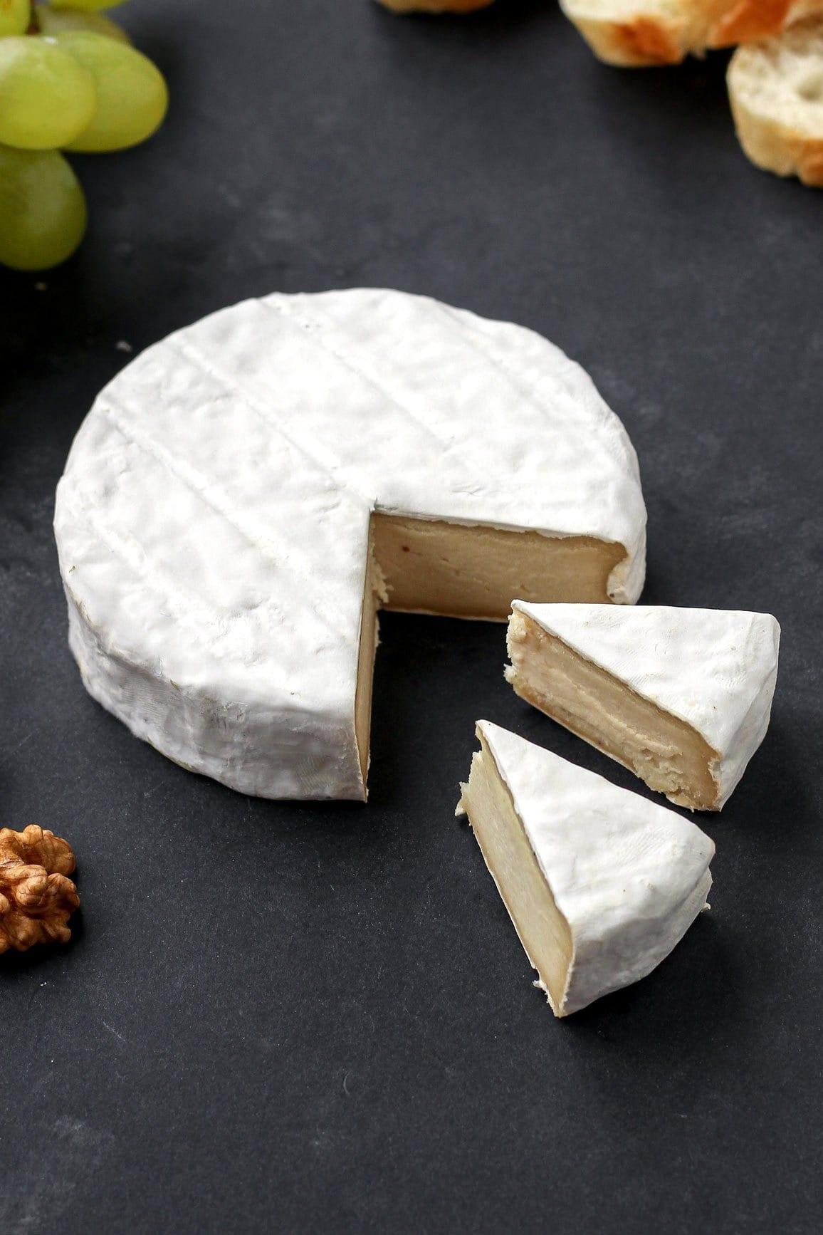 Slices of vegan camembert cheese on a black background.