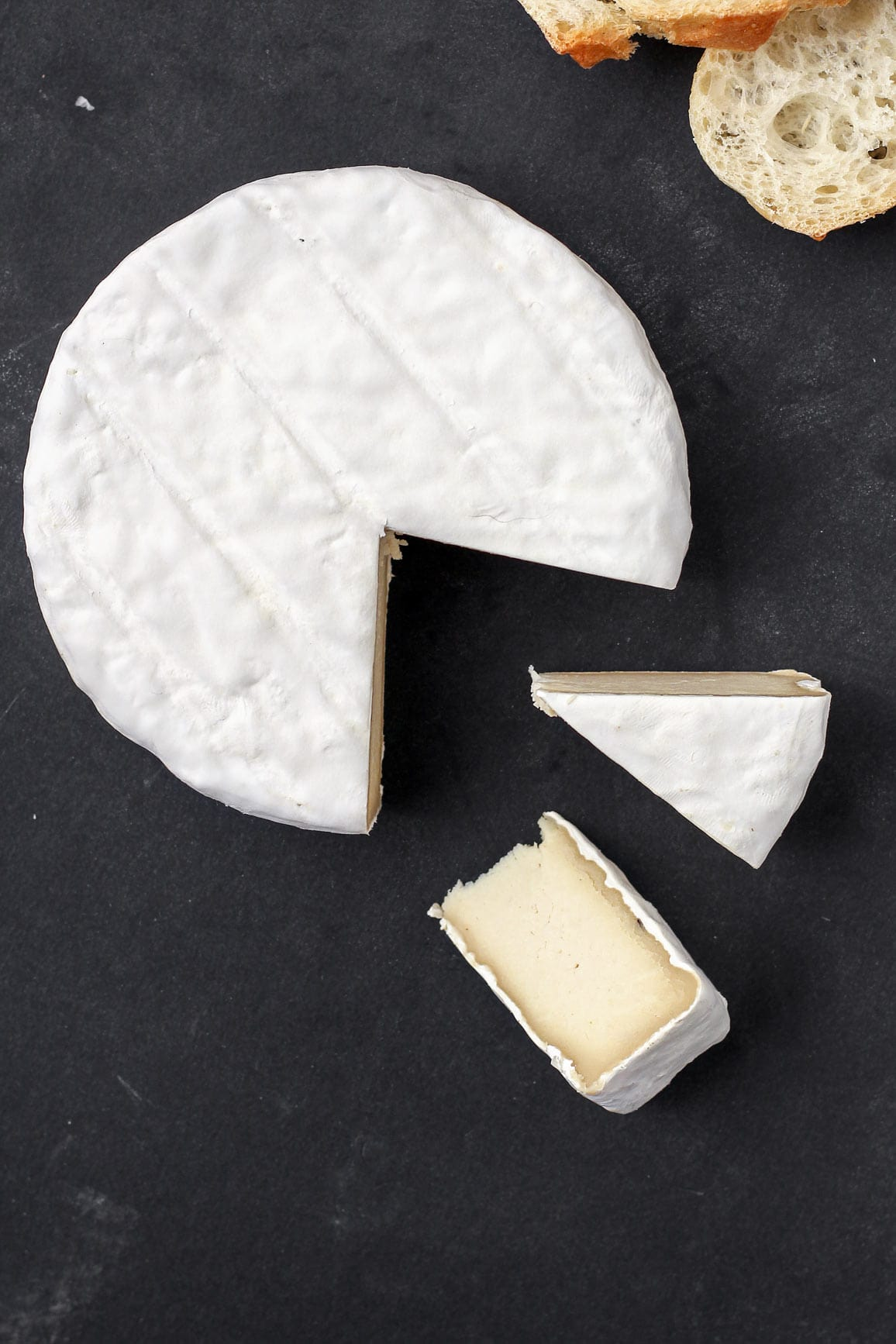 Vegan Aged Camembert Cheese on a black background.