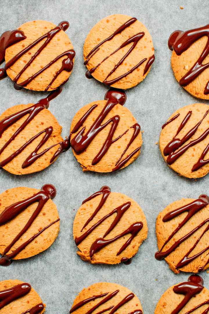 Vegan shortbread cookies on a baking sheet, drizzled with melted chocolate.