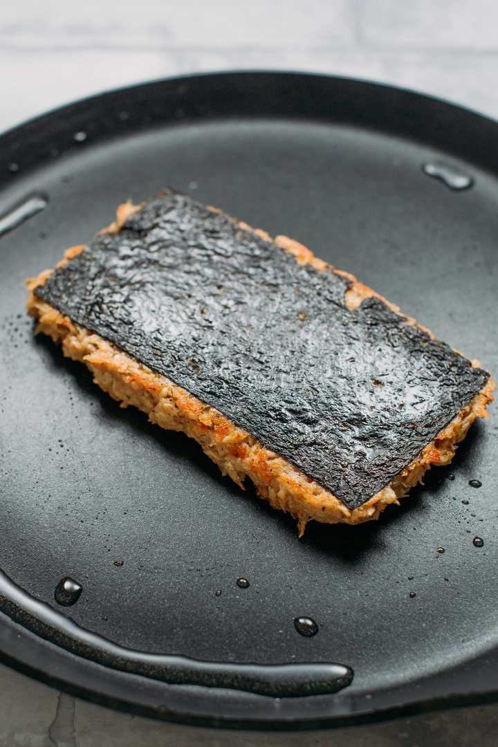 Vegan Fish Fillet sautéed in oil in a skillet.