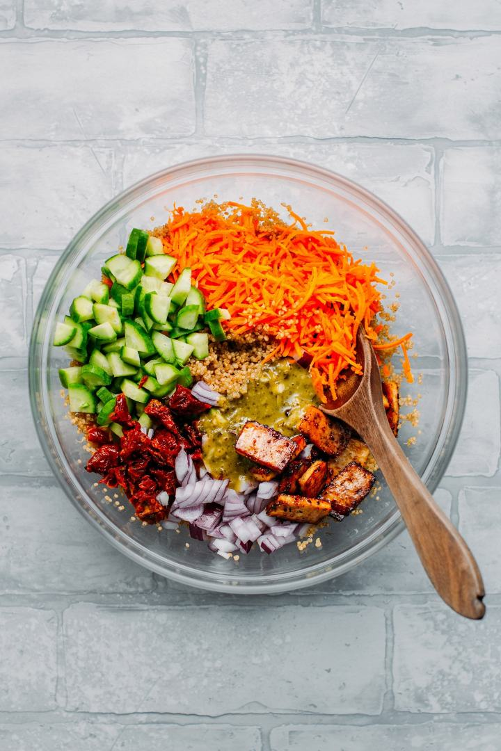 Cucumber, carrots, quinoa, tofu, and pesto to make salad.
