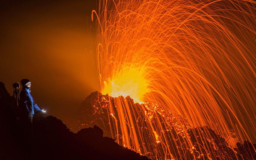 30. Турист наблюдает извержение вулкана Питон-де-ла-Фурнез.