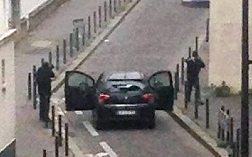 8. Вооруженные боевики обстреливают полицейских возле офисов французской сатирической газеты Charlie Hebdo в Париже. Фото: AFP / Getty Images.