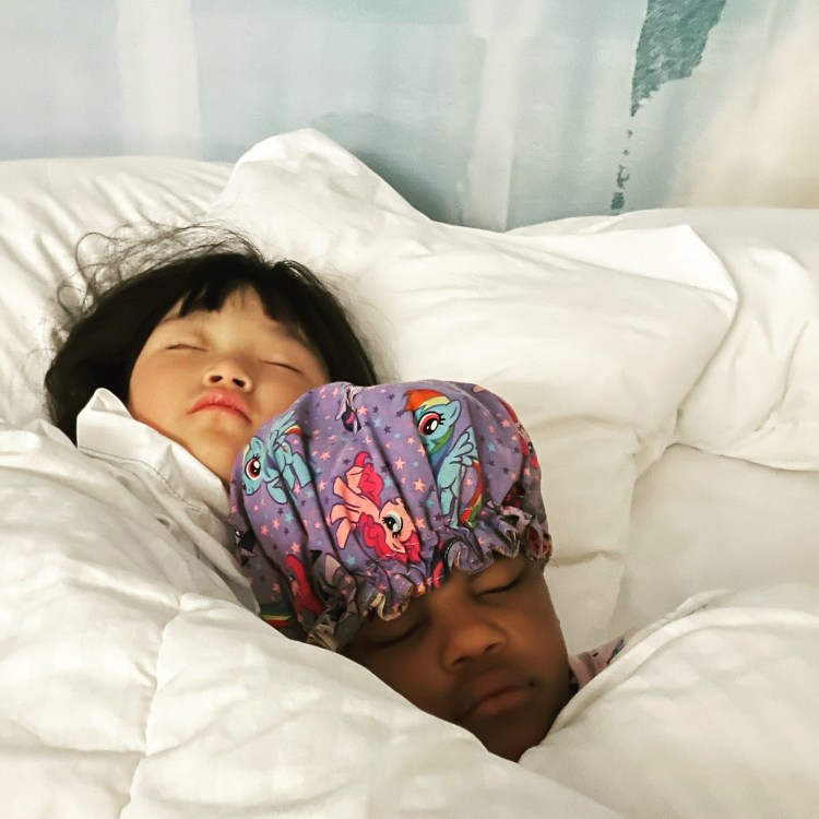 Two small girls, one Asian and one Black, are tucked together into a bed with white linens. They are sound asleep and cuddling.