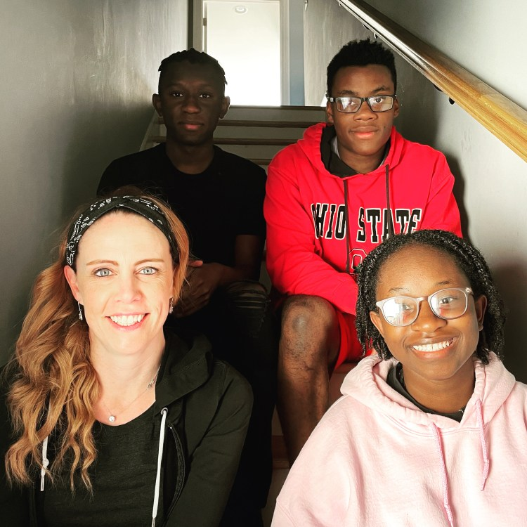 FPM, Becky, a white woman, sitting on the stairs with her eldest children, all Black. Ally is a Black woman in a pink hoodie with her hair in twists. Cam is a Black man with short hair in a red hoodie. AJ is a Black man with his hair in short twists. He is wearing a black tee.