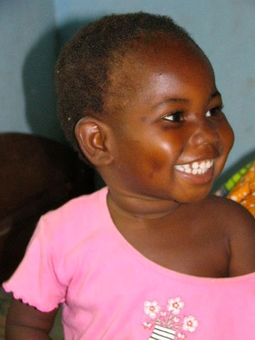 Image of a small African girl smiling broadly. She is wearing a pink shirt that has fallen off of her shoulder.