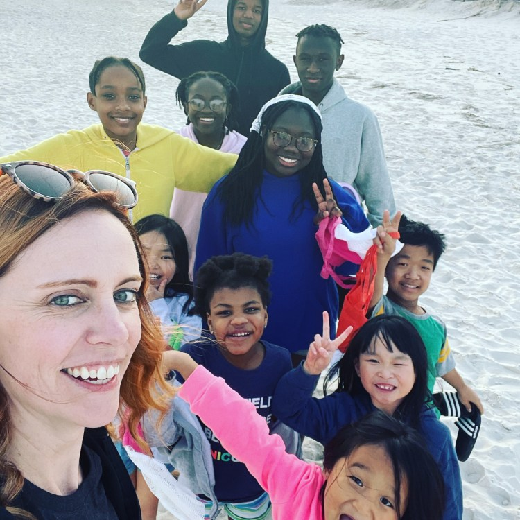 A selfie of FPM, Becky, on the beach. Behind her are all here children making funny faces and holding up peace signs.
