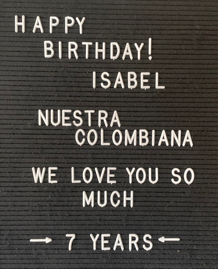 An image of a letter board with the words 'Happy Birthday Isabel, Nuestra Colombiana, We love you so much, 7 years' on it in white letters.